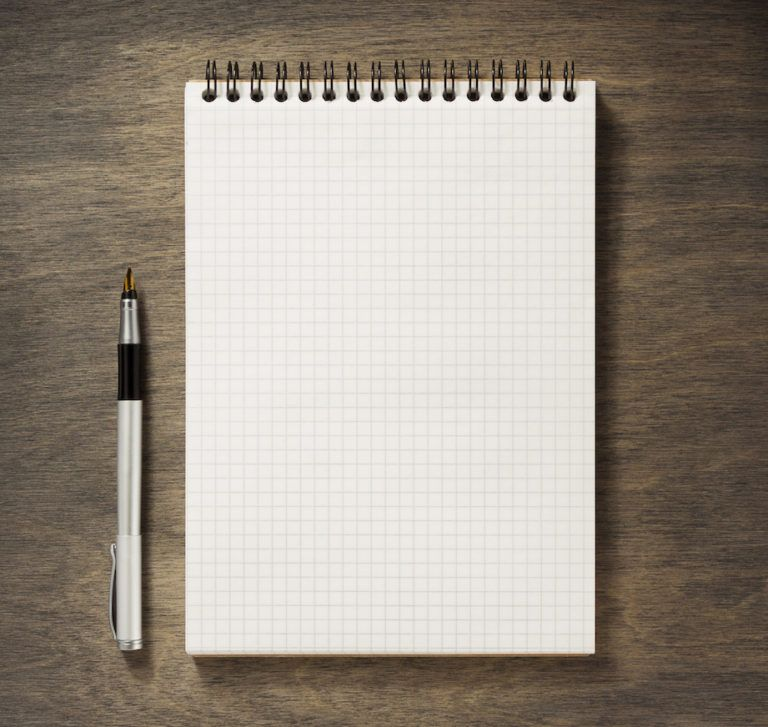 checked notebook and pen at wooden background