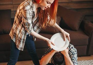Angry woman breaking dishes, family quarrel, agressive girl. Husband and wife in conflict. Problem relationship