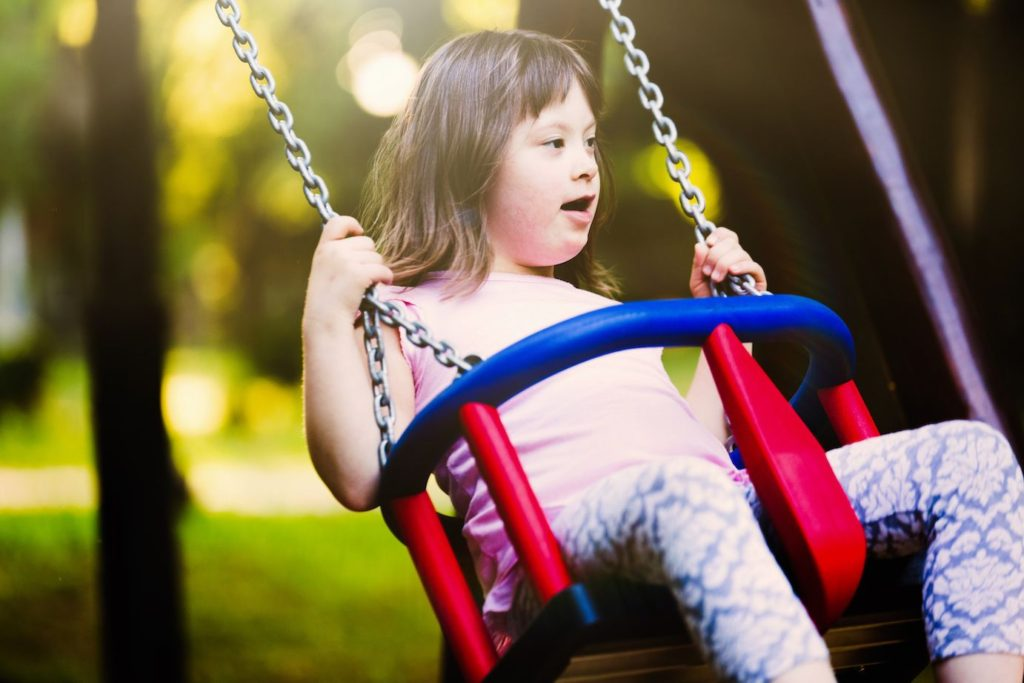 Portrait of young girl on swing with down syndrome