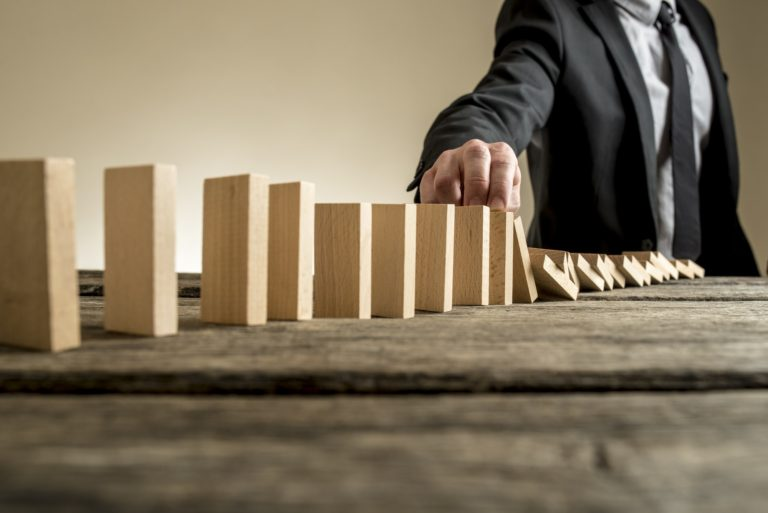 Businessman stopping domino effect with his finger