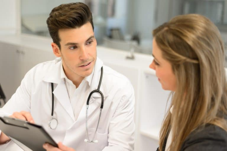 Doctor listening to patient explaining her painful in his office