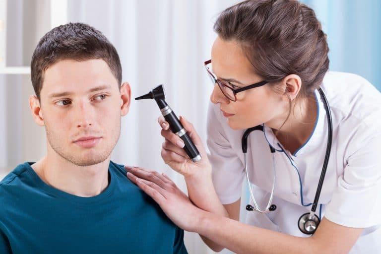 Young laryngologist examining
