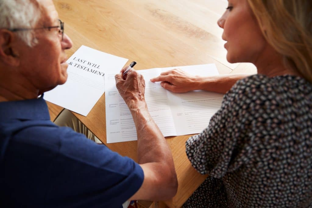 Woman Helping Senior Man To Complete Last Will And Testament At Home