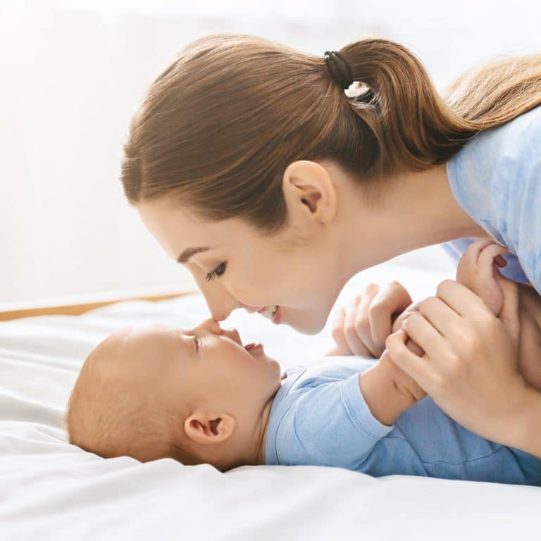 Mother and baby touching noses in bed, having fun together