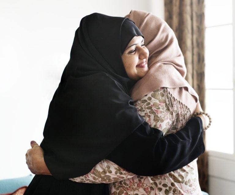 Muslim women hugging each other